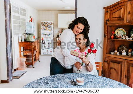 latin young woman and her mother middle age with flowers and gift box at home celebrating Happy mother's day in Mexico city