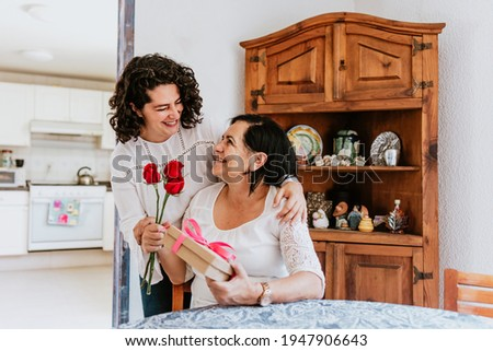 latin young woman and her mother middle age with flowers and gift box at home celebrating Happy mother's day in Mexico city Stok fotoğraf ©