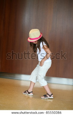 latina girl child with hat dancing hip hop moves