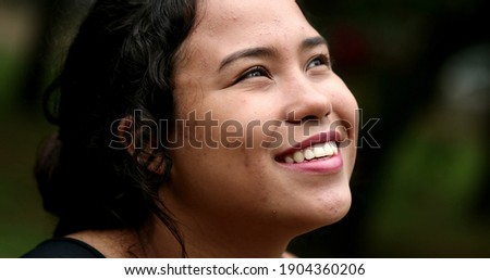 Latina girl looking at sky smiling. Hispanic young woman close-up face with HOPE and FAITH ストックフォト ©