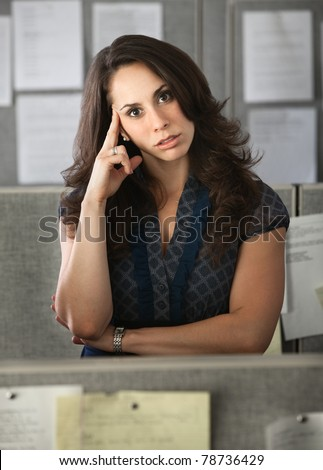 Latina office worker in a cubicle with hand on head