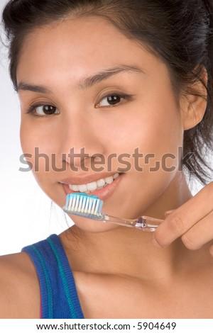 Latina teenager girl brushes her teeth