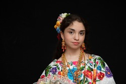 Latina teenager Mexican, dancer with typical costume from Yucatan Mexico, with black background, costume model embroidered with flowers in cross stitch handmade, with gold chains and coral beads