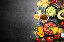 Latinamerican mexican food party sauce guacamole, salsa, chips and tequila on black table. Top view copy space.