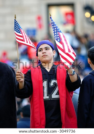 Latino boy holding American flags at pro immigration rally in Boston, Massachusetts. April 10, 2006.