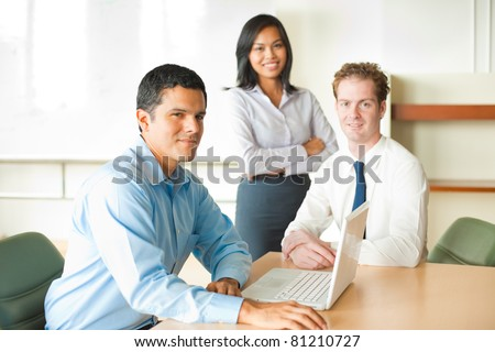 Latino businessman leader sitting at desk on laptop in conference room desk, meeting with diverse team of business people, attractive Asian woman and Caucasian male looking at camera. Horizontal