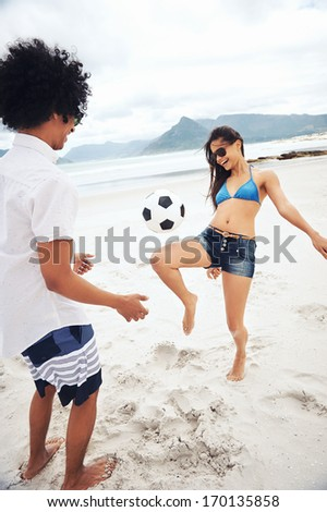 Latino Couple Playing Soccer On Beach With Ball Kicking And Having Fun