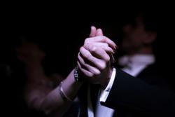 Latino dancers hands in ballroom  on black background