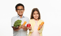 Latino girl and African American boy are holding broccoli, carrots, and an apple. Benefits of vegetables and fruits for children