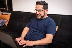 Latino man living with HIV sitting on his sofa using a laptop