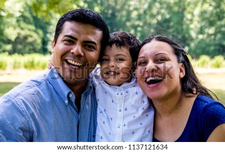 Latino parents with their son, smiling and laughing