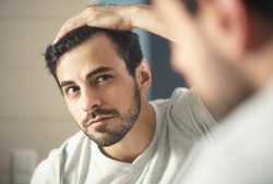 Latino person with beard grooming in bathroom at home. White metrosexual man worried for hair loss and looking at mirror his receding hairline.