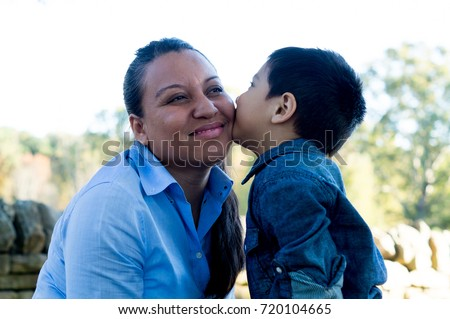 Latino son giving a kiss to his mother