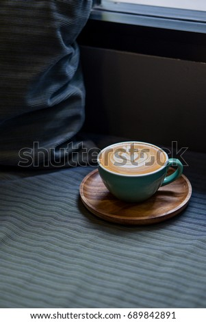 Latte art coffee in white cup on the wooden plate in bed room #689842891
