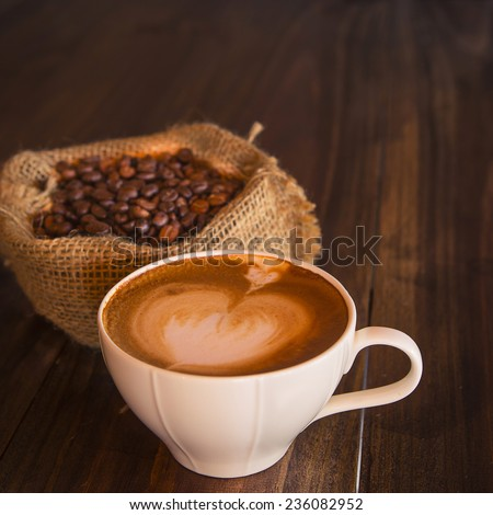 Latte art coffee with coffee bean on wood table  vintage style