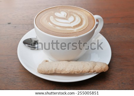 latte art coffee with heart pattern in a white cup and cookie on wooden background