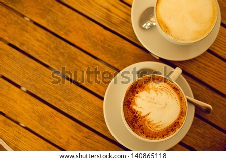 Latte art concept. Two cups with cappuccino (hot coffee with milk foam) and canella (cinnamon) on wooden table at street cafe (coffee bar). Vintage style. Outdoor shot.