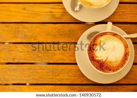 Latte art concept. Two cups with cappuccino (hot coffee with milk foam) and canella (cinnamon) on wooden table at street cafe (coffe bar). Vintage style. Copy-space. Outdoor shot.