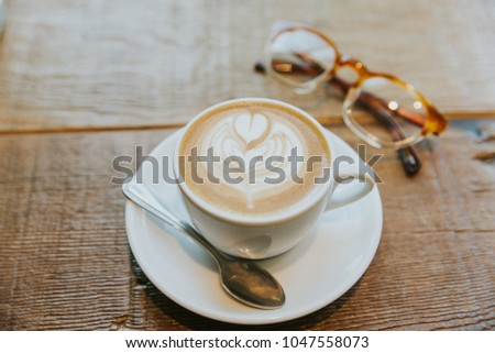 Latte art heart in simple white mug with plate and spoon on a wooden table with a pair of eye glasses #1047558073