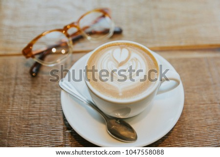 Latte art heart in simple white mug with plate and spoon on a wooden table with a pair of eye glasses #1047558088