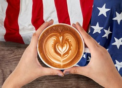 Latte art in a woman's hands With the flag of america on wooden background
