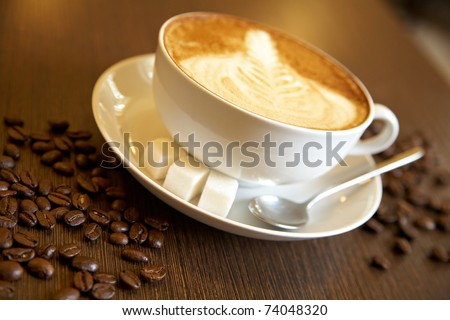 Latte art on a cappucinno and coffee-beans (selective DOF)