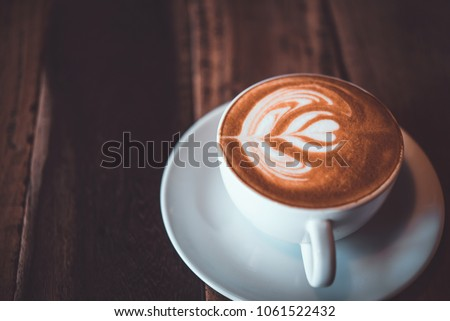 Latte arts coffe. White cup of hot coffee on wooden table. Cafe with barista art concept. #1061522432