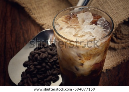 Photo of Latte ice coffee and coffee beans on rustic wooden table, Close up latte ice coffee, selective focus, free space for text and toned image.