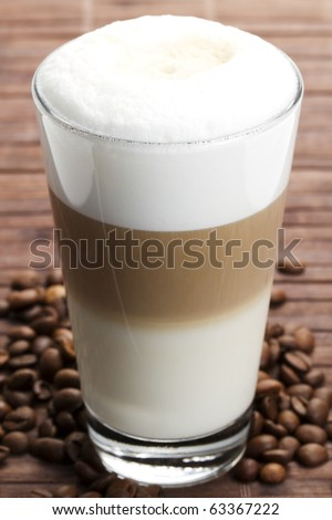 latte macchiato with coffee beans on wooden background