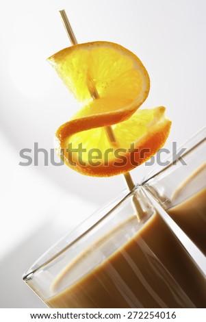 Latte Macchiato with orange peel on skewer