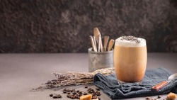 Latte or cappuccino with milk foam and lavender in a glass with coffee beans. Dark background