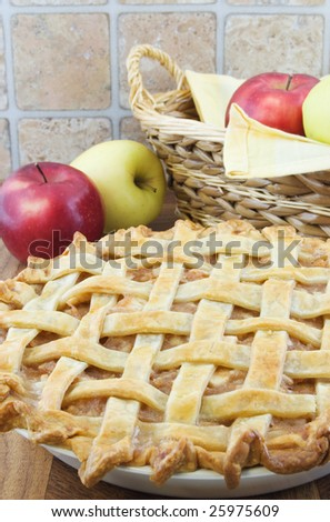 Lattice apple pie with apples and basket behind