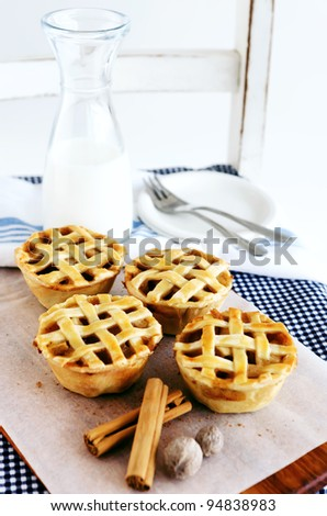 Lattice apple pies presented in a rustic way, on a wooden chair with checkered cloth and a beaker of milk