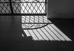 Lattice, grid infront of hard sunlight. Silhouette and shadow of iron fence. Texture background in black and white style.