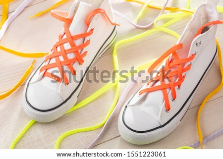 Lattice laced up white sneakers with orange shoelaces. Creative way to make plain shoes look cool. #1551223061