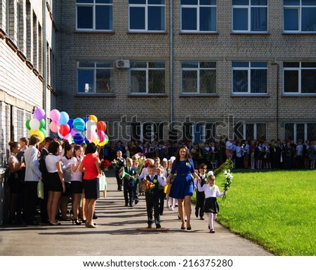 LATVIA, RIGA - September 1, 2014:  Children with flowers in front of the School No. 68 on the first day of school on September 1, 2014 in Riga, Latvia.