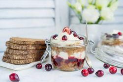 Latvian, scandinavian traditional rye whole grain bread layered dessert with whipped cream and cowberry jam served in glass jar on a white table with flowers and berries, copy space.