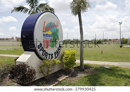 LAUDERHILL, FL, USA - JUNE 19, 2014: Large and colorful entrance sign for the Lauderhill Sports Park in front of a soccer field. The plastic sign also mentions that Lauderhill is an All-American City