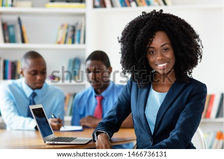 Laughing african african businesswoman with business team at office of company