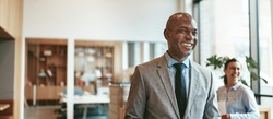 Laughing African American businessman walking in an office holding paperwork after a meeting with colleagues