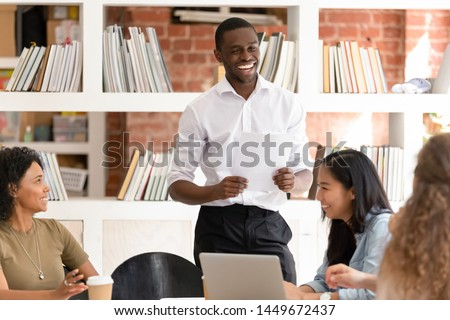 Laughing African American businessman with diverse employees group having fun at meeting, friendly business coach joking, happy team involved in funny team building activity, staff training