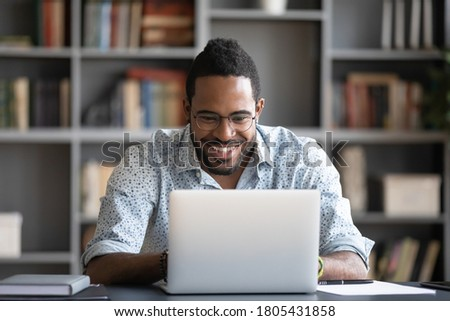 Laughing African American man using laptop, looking at screen, chatting with friends in social network, reading good news in email, funny young male watching video, having fun with computer
