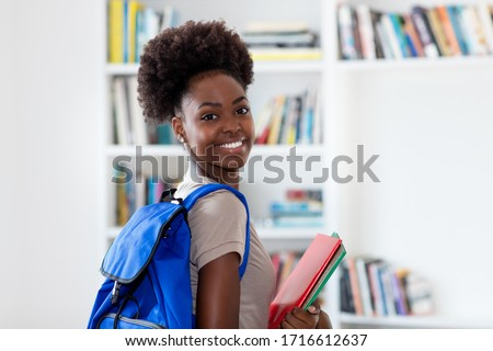 Laughing afro american female student with backpack and paperwork at classroom of university