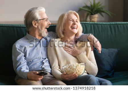 Laughing aged couple, man and woman watching tv, comedy show or movie and eating popcorn snack, sitting on cozy couch at home, mature family, man and woman enjoying free time, weekend together