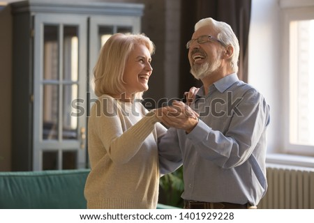 Laughing aged spouses holds hands standing in living room dancing at home, elderly family healthy active retirees celebrates anniversary chatting feels happy, forever love harmony in relations concept