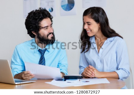 Laughing arabic business team at work at desk at office of company
