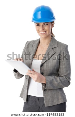 Laughing architect woman standing, wearing hardhat, with touchscreen computer handheld, looking at camera.