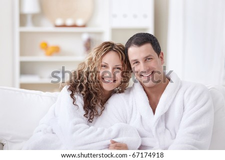 Laughing attractive couple in dressing gowns - stock photo