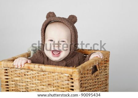 Laughing baby boy sitting in a basket wearing a fully bear suit