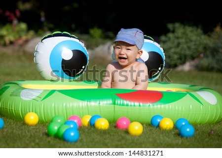 Laughing baby boy sitting in a kids rubber pool